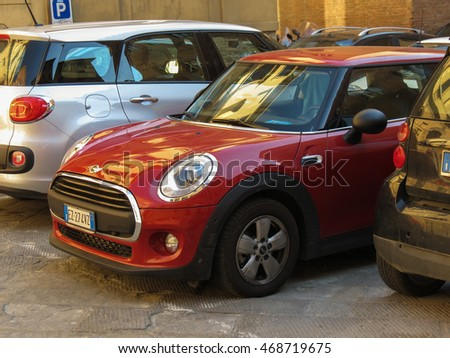 SIENA, ITALY - CIRCA JULY 2016: red Mini Cooper car parked on a street of the city centre