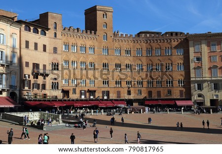 Siena, Italy - September 26, 2017: Tourists walking on the Piazza del Campo town square surrounded by historical buildings in Siena, Italy on September 26, 2017