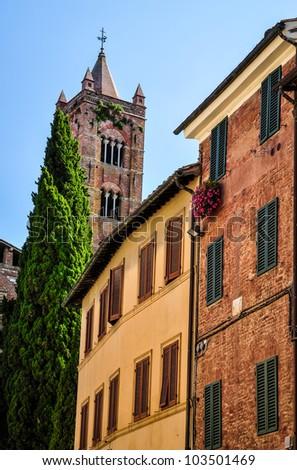 Siena street with Santa Maria di Servi tower - stock photo