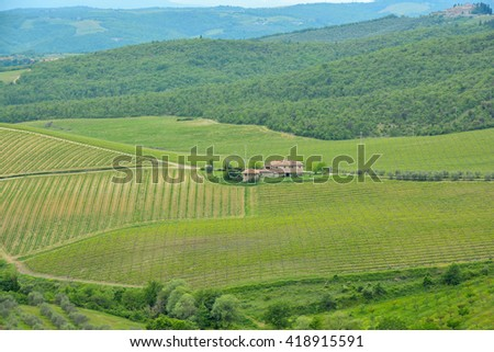 SIENNA, ITALY - MAY 08, 2016 - Landscape with hills of the Chianti farmhouses in the Tuscan in spring with rows of vines - stock photo