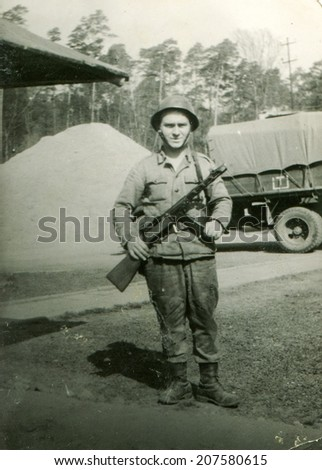 SIERADZ, POLAND, CIRCA SIXTIES - Vintage photo of soldier with a gun