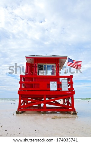 Siesta Key Beach, Florida USA, red lifeguard house with American flag on a beautiful summer day with ocean and blue cloudy sky