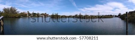 Siesta Keys Canal area panoramic.  Featuring calm waters, wood pier and fancy houses in the distant - stock photo