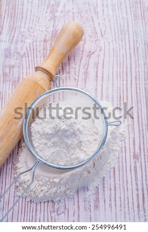 sieve with white natural flour and wooden rolling pin on vintage desk food and drink concept  - stock photo