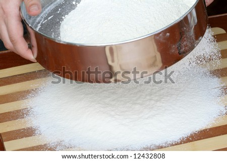 Sifting a flour on wooden board, background