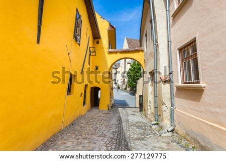 Sighisoara, Romania - June 23, 2013: Old stone paved street with tourists from Sighisoara fortress, Transylvania, Romania