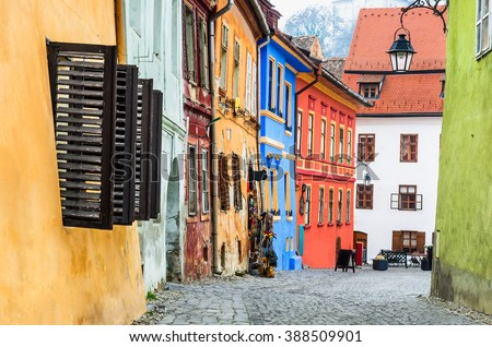 Sighisoara, Romania. Stone paved old streets with colorful houses in Sighisoara fortress, Transylvania region of Europe - stock photo