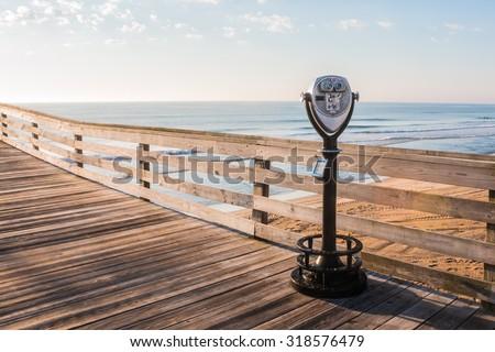 Sightseeing Binoculars with Beach Background on the Virginia Beach Fishing Pier - stock photo