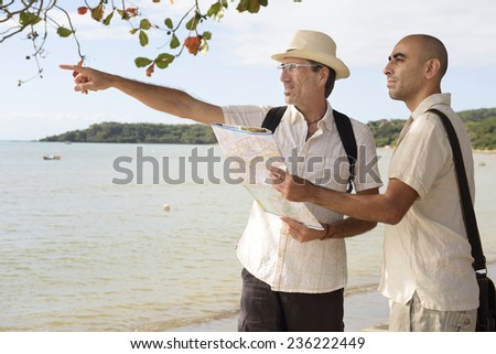 Sightseeing: Gay couple on vacation pointing at destination