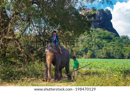 SIGIRIYA, SRI LANKA - 28 FEBRUARY, 2014: Japanese tourist riding on the back of elephant and mahout standing at rear with rock of Sigiriya as backdrop. Sigiriya is UNESCO listed World Heritage Site. - stock photo