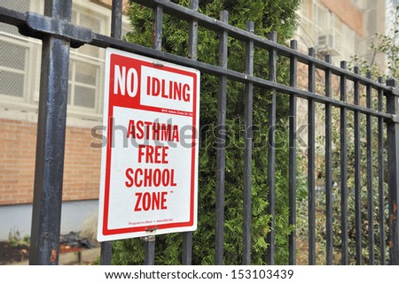 Sign at a fence of a school in New York.The text tells the people that this is a zone that has as low asthma causing dust as possible
