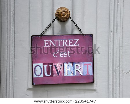 "sign at a shop with the french text: ""entrez c'est ouvert"" that means ""come in we're open"" - stock photo"