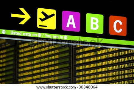 Sign at airport showing the route to the gates.With Spanish and English text.At background arrival and departure board - stock photo