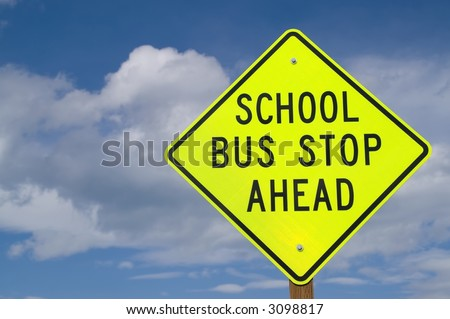 Sign at right of photo warning of school bus stop ahead...often found on rural roads - stock photo