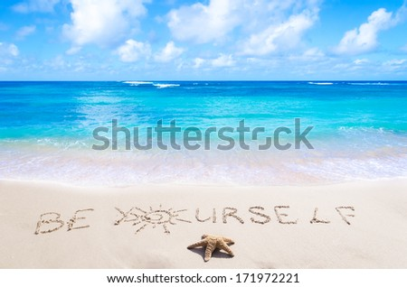 "Sign""Be Yourself"" with starfish on the sandy beach by the ocean"
