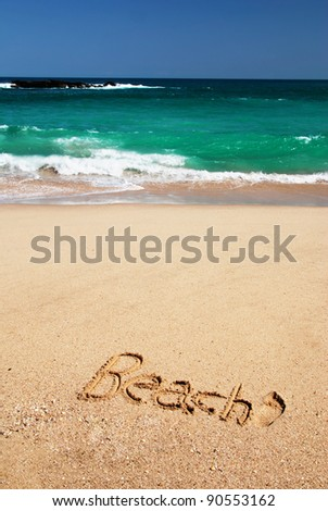 "Sign ""Beach"" written in the sand of the tropical beach of Sri Lanka near the azure sea - stock photo"