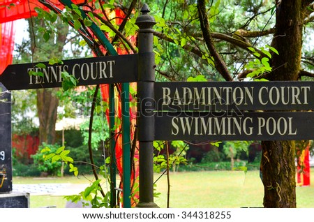 Sign board set against trees, showing various fitness options like tennis, badminton and swimming. These are available in resorts and are a great option for non gym goers