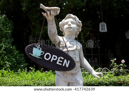 sign cafe open by child statue in a garden - stock photo