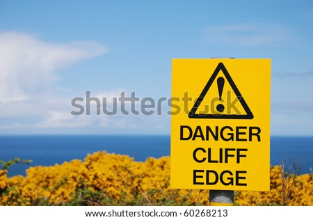 sign danger cliff edge on the Antrim cliffs yellow with goarse in spring - stock photo