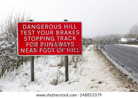 Sign depicting an escape lane ahead for out of control vehicles descending a steep hill in wintry conditions - stock photo