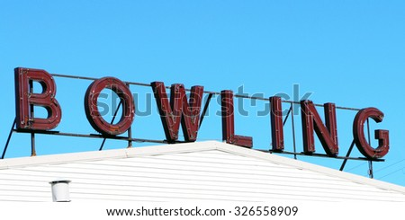 """Sign for """"bowling"""" in neon letters atop an old bowling alley. - stock photo"""