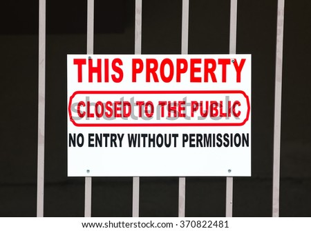 Sign hanging off a metal rod fence, informs that this property is closed the public.  - stock photo