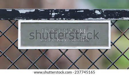 Sign hanging on an old metallic gate - Dont ignore opportunities