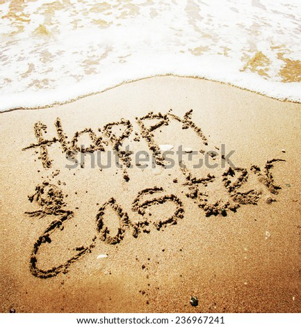 "Sign ""Happy Easter"" on the sandy beach by the ocean"