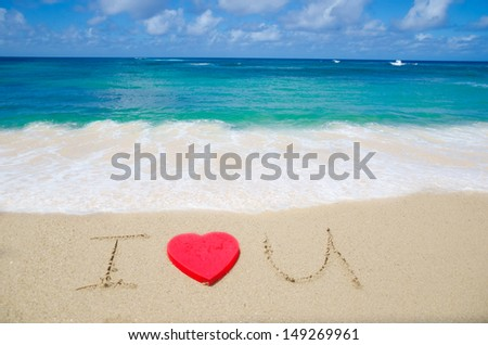 "Sign ""I Love U"" with red heart shape on the beach"