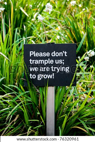Sign in a public park instructing visitors not to trample plants.