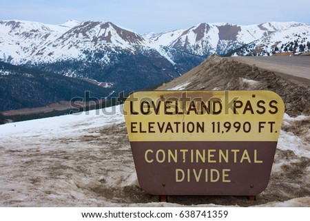 Sign marking Loveland Pass Continental Divide in Colorado Rocky Mountains with snow covered peaks in the background