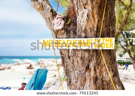 Sign nailed to a tree on the beach at Rum Point, Grand Cayman - stock photo