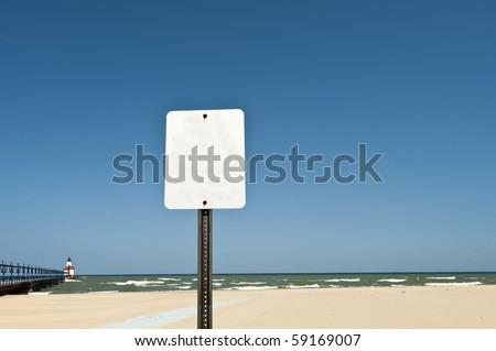 Sign near beach with St. Joseph, MI pier in the distance - stock photo