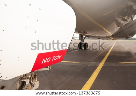 Sign NO TOW on undercarriage of airplane while waiting on runway - stock photo