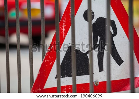 Sign of a construction site at a street behind a fence/Roadworks