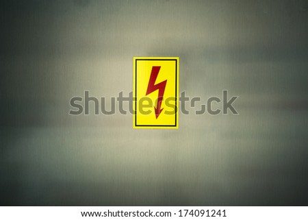 sign of danger high voltage symbol on the metal wall - stock photo