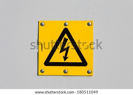 Sign of danger high voltage symbol on the white wall - stock photo