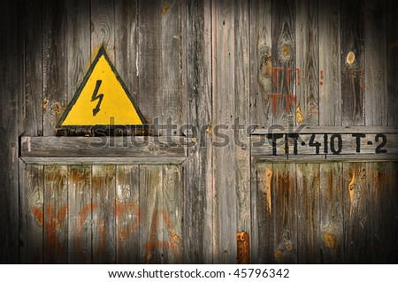 sign of danger of electricity on old wooden doors - stock photo