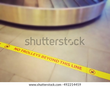 "Sign of ""No trolley beyond this line"" in the airport, luggage drop area, vintage effect"