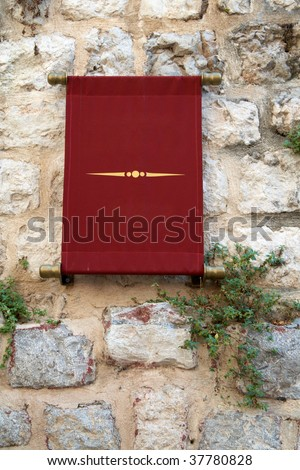 sign of the red cloth on an old stone wall - stock photo