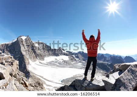 Sign of victory: climber on the top of the mountain. Gran Paradiso National Park, Italy - stock photo