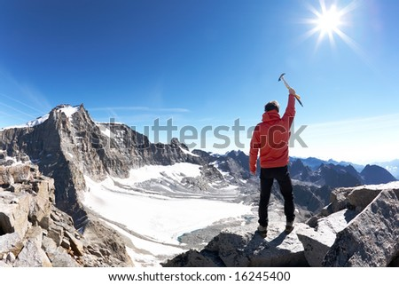 Sign of victory: climber on the top of the mountain. Gran Paradiso National Park, Italy