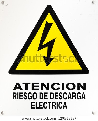"Sign of warning for high voltage or ""atencion riesgo de descarga electrica"" in spanish. This is a photo of a real sign and it is not intended to be an isolation. The white on it is not blown. - stock photo"