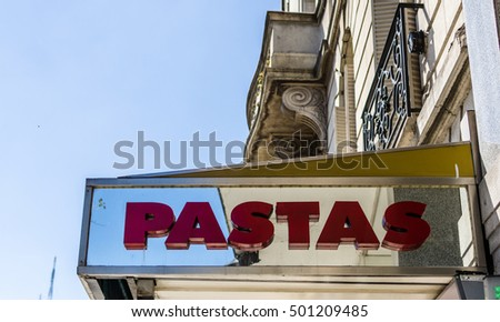 Sign on a building saying pastas against blue sky
