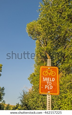 Sign on a walking path to let bicyclists know they are supposed to yield to pedestrians.
