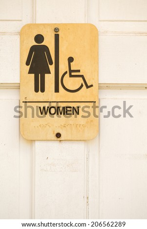 Sign on a white door to womens restrooms.