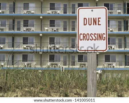 Sign on beach beyond hotel (focus on sign)