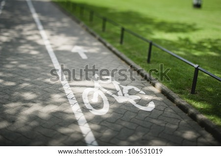 Sign on bike lane. Tilt shift lens used to accent the bike and to emphasize the attention on it. - stock photo