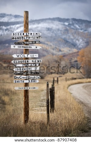 Sign on country road in the mountains with snow - stock photo