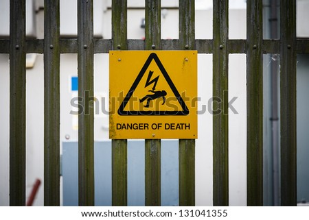 Sign on fence danger of death - stock photo